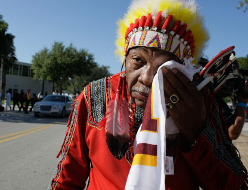 "MIAMI - DECEMBER 03: Washington Redskins ""unofficial"" mascot Zema Williams known as Chief Zee wipes his face as he arrives for the funeral of Redskins football player, Sean Taylor, at the Pharmed Arena at Florida International University December 3, 2007 in Miami, Florida. Taylor died November 27, one day after being shot at his home in Miami. (Photo by Joe Raedle/Getty Images)"